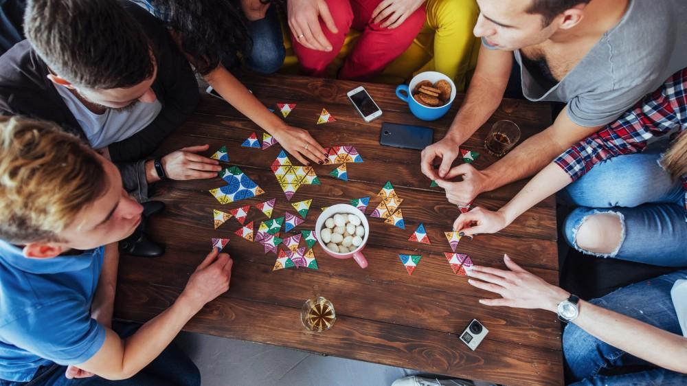 منظر علوي لصورة إبداعية لأصدقاء يجلسون على طاولة خشبية يلعبون لعبة لوح مع وجبات خفيفة ومشروبات