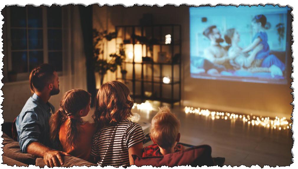 والد العائلة والأطفال يشاهدون فيلم الفشار على جهاز العرض في المنزل ليلاً