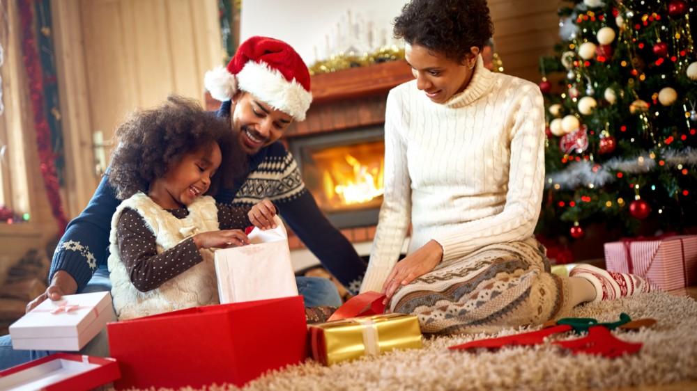 يشاهد الآباء أطفالهم وهم يفتحون هدايا عيد الميلاد أمام المدفأة وشجرة عيد الميلاد