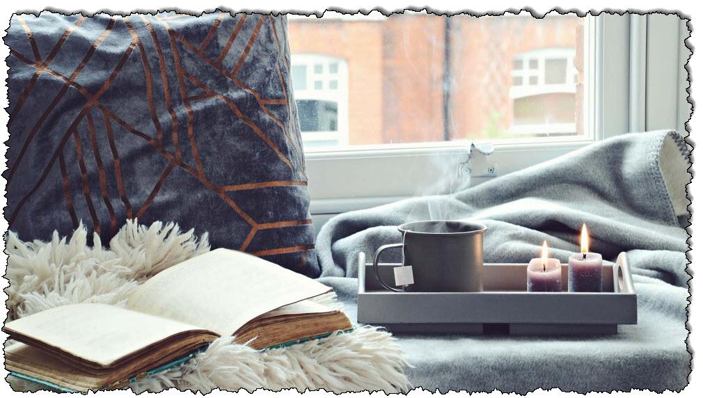توجد وسادة وبطانية غير واضحة وكتاب وصينية بها شمعتان وكؤوس على مقعد النافذة.