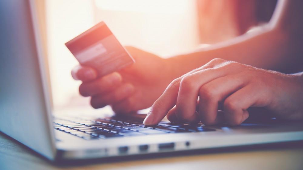 أيدي تحمل بطاقات الائتمان والتسوق على الكمبيوتر المحمول