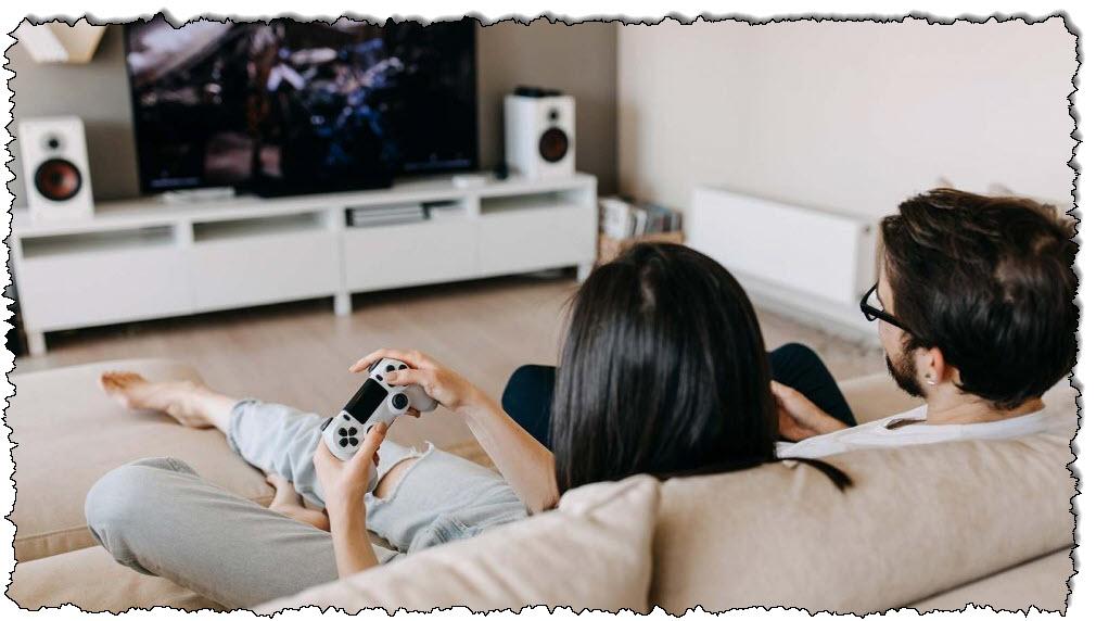 زوجان يرقدان على الأريكة ويلعبان ألعاب الفيديو معًا.