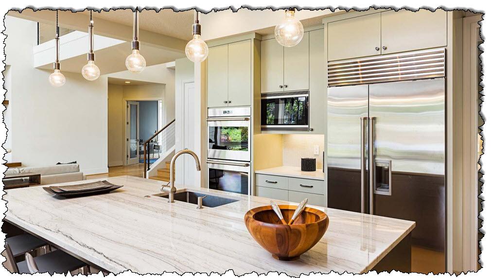 مطبخ حديث جميل بطاولات رخامية وأجهزة راقية.