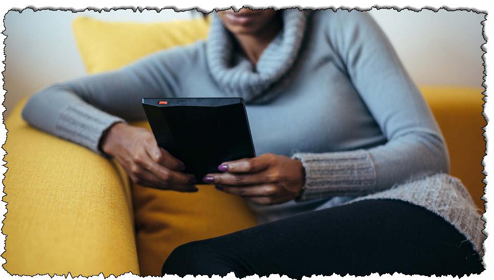 امرأة تقرأ قارئ كتب إلكترونية ، مسترخية على أريكة صفراء.