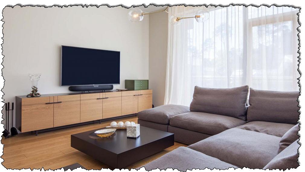 تحتوي غرفة المعيشة العصرية على مجموعة أرائك وتلفزيون بشاشة مسطحة.