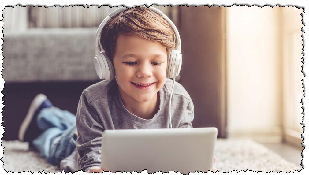 صبي يستمع إلى سماعات الرأس أثناء استخدام الجهاز اللوحي في غرفة معيشة مشمسة.