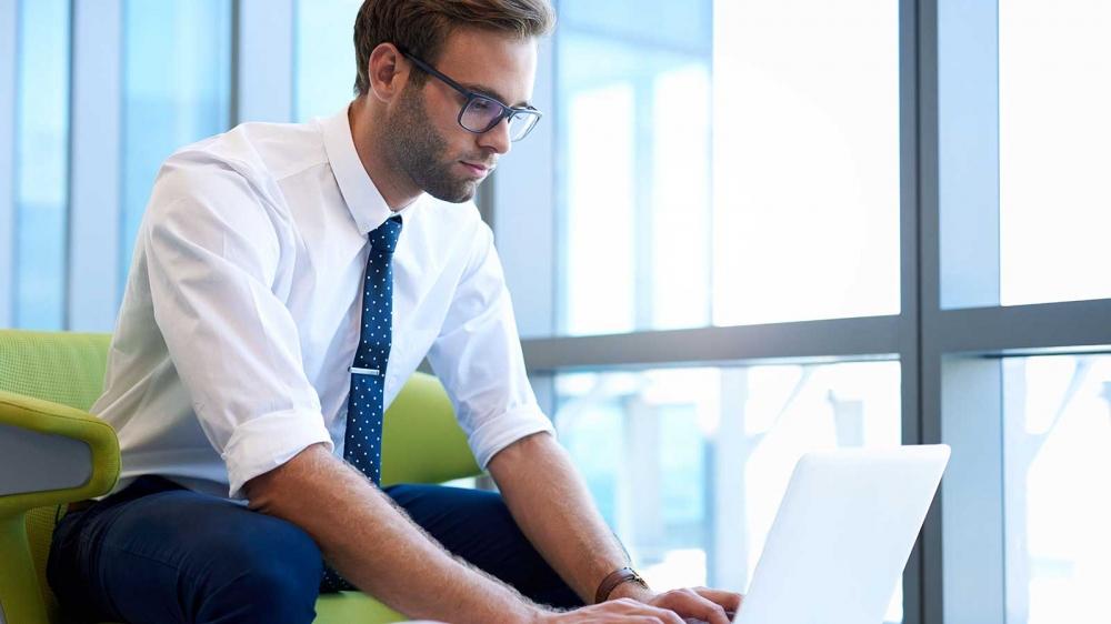 رجل في ملابس العمل يعمل على جهاز الكمبيوتر المحمول الخاص به.