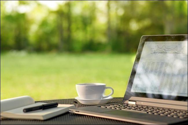 كمبيوتر محمول وقهوة على طاولة خارجية