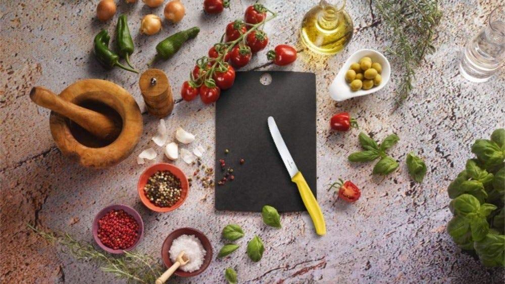 لوح تقطيع أسود صغير بسكين تقطيع مسنن فيكرز والعديد من المكونات العطرية حول لوح السكين.