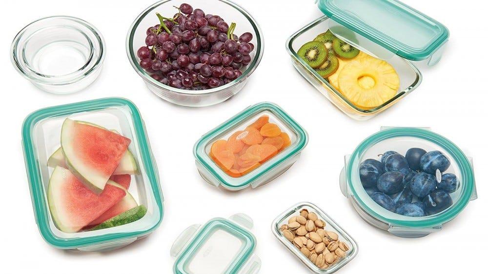 أوعية تخزين طعام زجاجية مختلفة من OXO مليئة بأطعمة مختلفة على خلفية بيضاء.