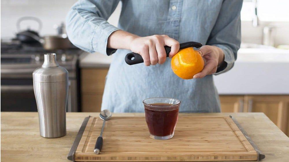 شخص ما يقوم بتقشير البرتقال ، ويستعد لعمل كوكتيلات قديمة الطراز.