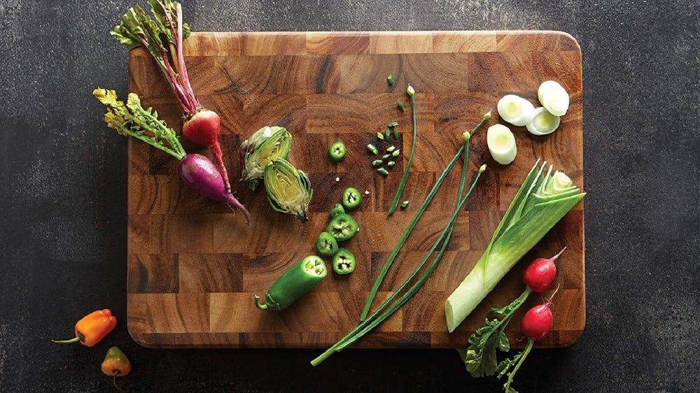 تستخدم Ironwood Gourmet لوح تقطيع خشبي محبب مصنوع من خشب الأكاسيا مع مجموعة متنوعة من الخضار عليه.