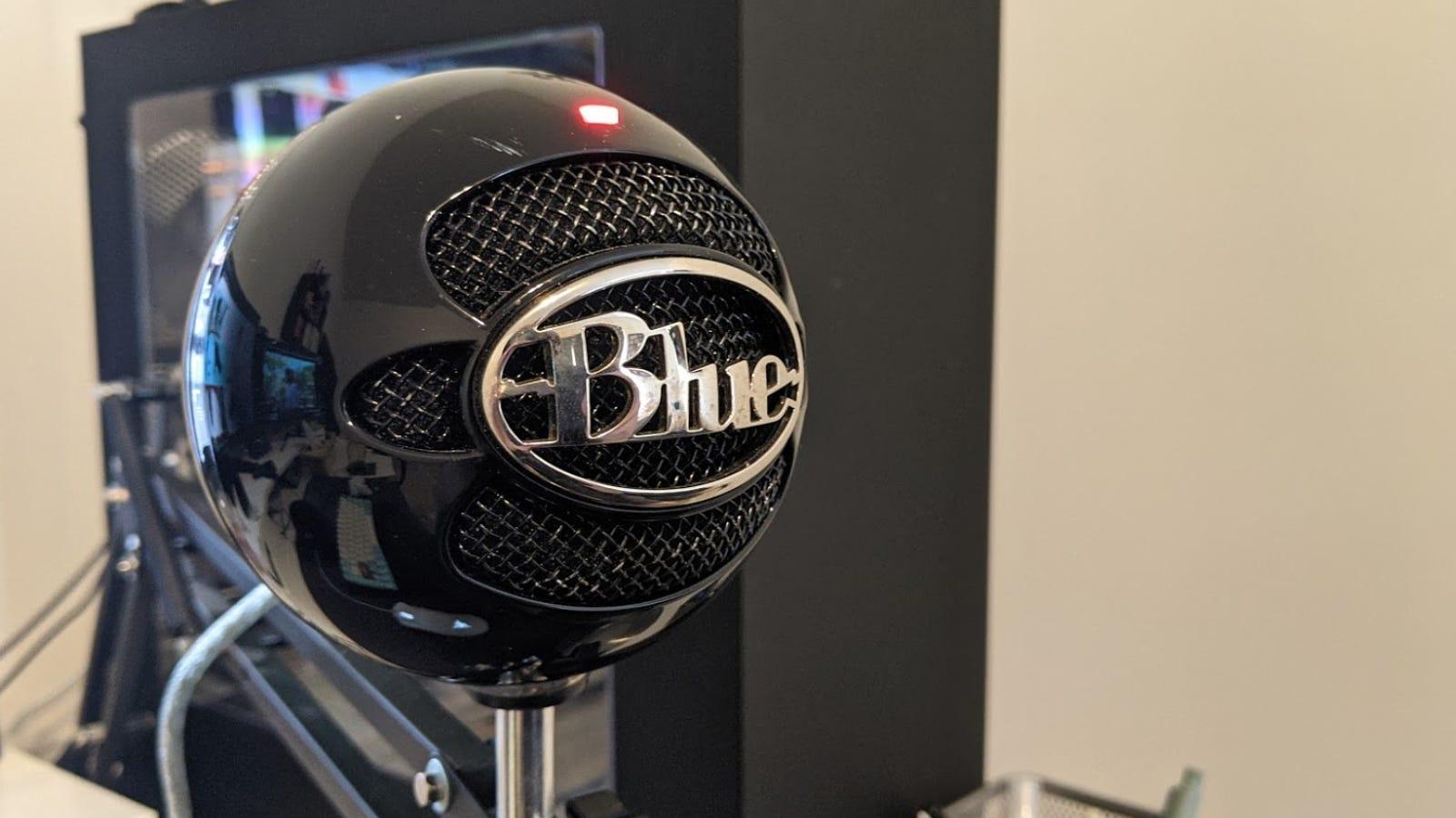 ميكروفون كرة ثلج أزرق على الرف بجوار الكمبيوتر