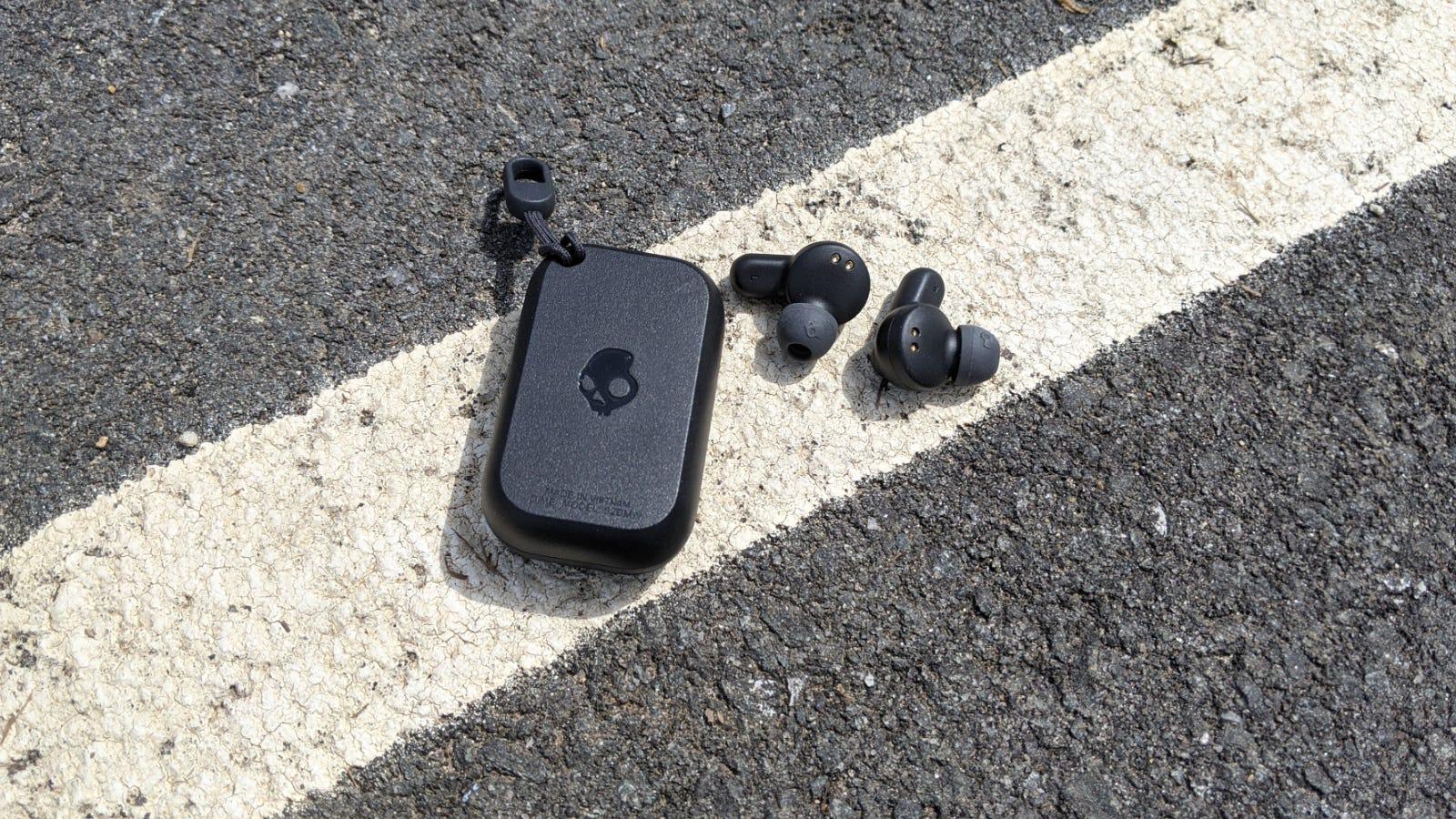 تم فصل حافظة الهاتف وسدادات الأذن من Skullcandy Dime على الرصيف