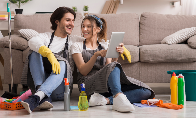 Cheerful young couple pausing from cleaning to use an app on a tablet