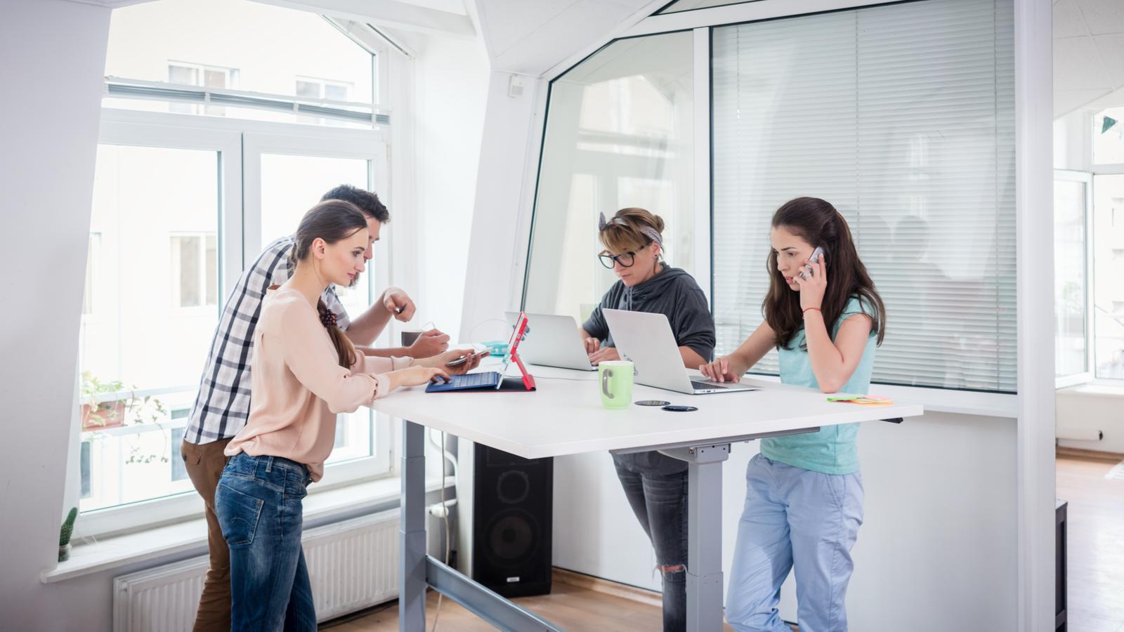 الزملاء المشغولون يستخدمون تقنية الهاتف المحمول أثناء مشاركة المكاتب في المساحات المكتبية الحديثة