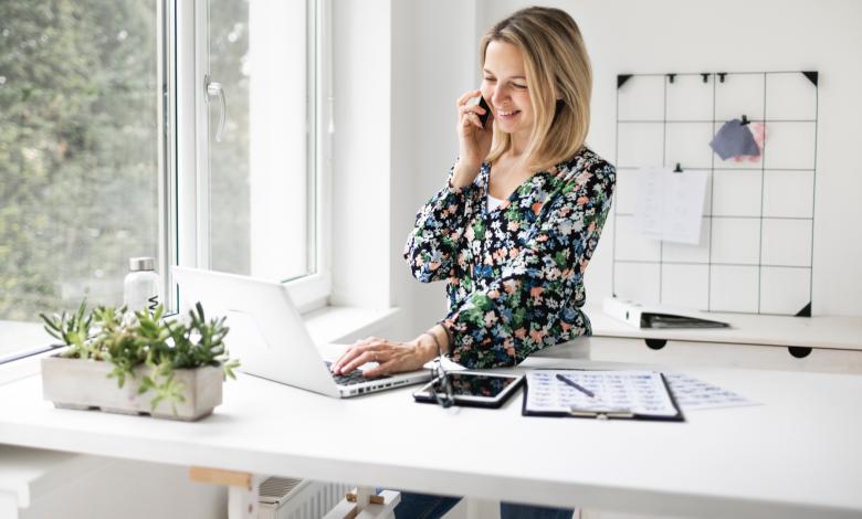 Businesswoman using phone while working at ergonomic standing desk