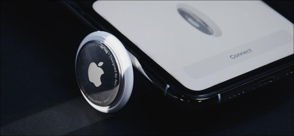 مجموعة من علامات AirTags بجانب iPhone.