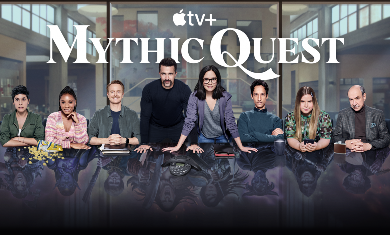 The cast of Mythic Quest behind a conference table.